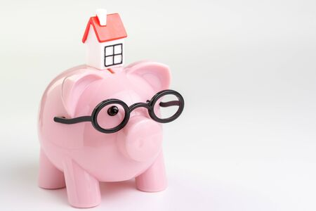 House maintenance budget, cost, savings or mortgage home loan concept, miniature house on pink piggy bank wearing glasses on white background with copy space.