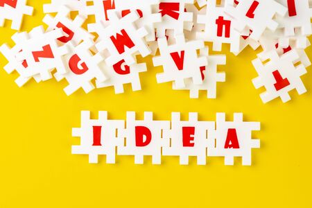 White puzzle jigsaws with alphabets building word IDEA at the center of other alphabets on yellow background, business idea, creativity or inspiration in work and problem solving. Reklamní fotografie