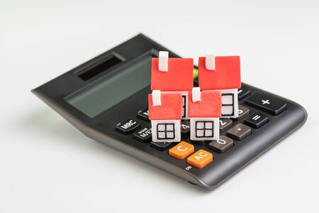 House cost calculation, mortgage and home loan or real estate price concept, group of miniature houses with red roof on black clean calculator on white background. Фото со стока