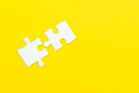 2 jigsaw puzzle on solid yellow background using as 2 important thing combine or working together to success or solve problem. 版權商用圖片