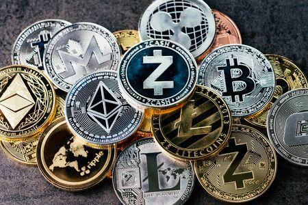 Kryptowährungshintergrund mit verschiedenen glänzenden silbernen und goldenen physischen Kryptowährungssymbolmünzen, Bitcoin, Ethereum, Litecoin, Zcash, Ripple.