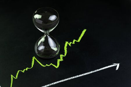 Time for invest or long term investment concept, hourglass or sandglass with black sand inside on stock market green line rising chart drawing with chalk on black chalkboard. Stockfoto