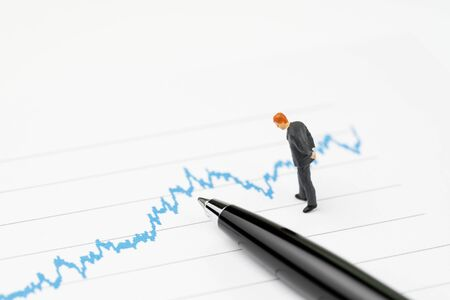 Financial performance graph analysis concept, miniature professional businessmen standing and looking, review on volatility blue stock market line graph data report with pen.