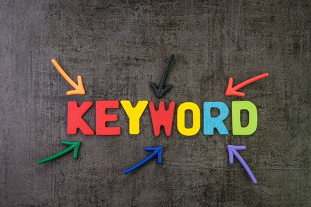 Keywords research for SEO, Search Engine Optimization, bidding on search result page to promote website online, multi color arrows pointing to the word Keyword at the center of black cement chalkboard wall.