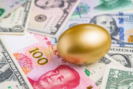 Shiny golden egg on pile of Chinese Yuan and US America dollar banknotes money metaphor of finding the good stock with high dividend or success investment in stock market from trade war concept.