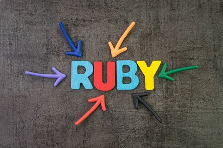 Ruby modern programming language for software development or application concept, multi color arrows pointing to the word Ruby at the center of black cement chalkboard wall. Stock Photo