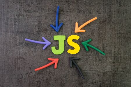 JS, Javascript modern programming language for software development or application concept, multi color arrows pointing to the word JS at the center of black cement chalkboard wall.