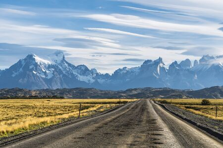 Beautiful view of rural road with golden yellow grass with background of nature cuernos mountains peak with cloud in autumn, Torres del Paine national park, south Patagonia, Chile.