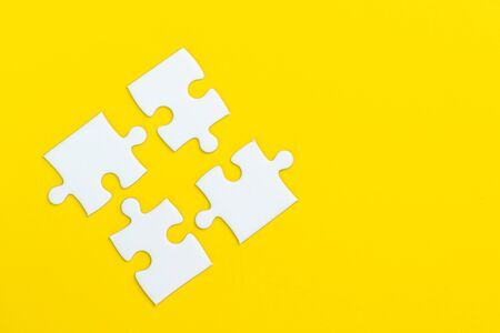 4 jigsaw puzzle on solid yellow background using as four important thing combine or working together to success or solve problem.