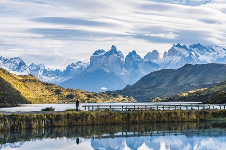 Beautiful panoramic view small people standing at the dock from the lake with Cuernos, horn mountains peak with lenticular cloud in autumn, Torres del Paine national park, south Patagonia, Chile.