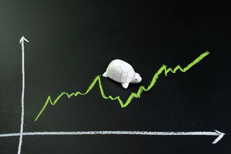 Slow but stable investment or low fluctuate stock market concept, miniature figure turtle or tortoise walking on chalkboard with drawing green price line graph of stock market value. 免版税图像