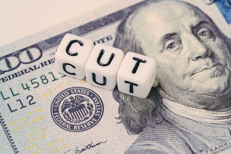 FED, Federal Reserve con il concetto di taglio del tasso di interesse, piccolo cubo con alfabeto che costruisce la parola CUT accanto all'emblema della Federal Reserve sulla banconota del dollaro USA. Archivio Fotografico
