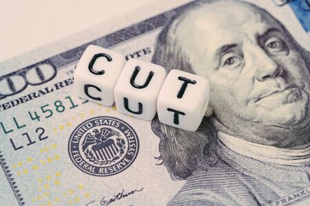 FED, Réserve fédérale avec concept de réduction des taux d'intérêt, petit bloc cubique avec alphabet construisant le mot CUT à côté de l'emblème de la Réserve fédérale sur un billet en dollars américains. Banque d'images