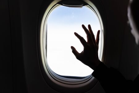 Hand on airplane window with aerial view of white clouds with silhouette man face look outside. 版權商用圖片