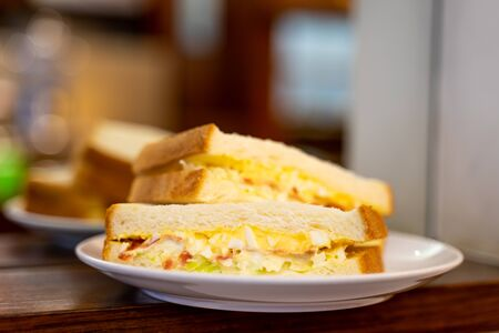 Closed up of morning sandwiches with egg, ham and vegetable on white dish in coffee shop. Stock Photo