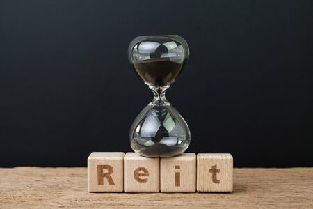 REIT, Real estate investment trust booming time concept, sandglass or hourglass on wooden cube block with alphabet building the word Reit on wood table, dark black background.