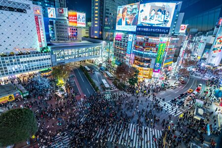 Shibuya, Tokyo, Japan - December 24, 2018: Top view of crowd people pedestrians walking across zebra crosswalk in Shibuya district at night in Tokyo, Japan. Lights from commercial billboards.