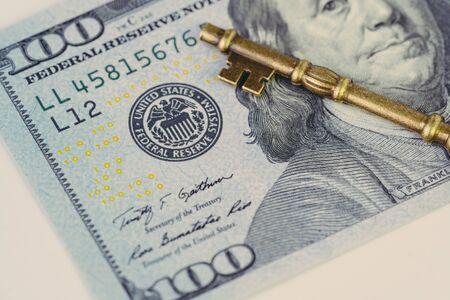 FED, Federal Reserve of US government direction on interest rate concept, vintage bronze key on US Dollar banknote with Feral Reserve emblem.