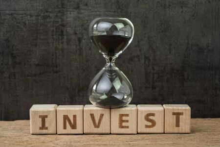 Long term investment, countdown to crisis or stock market timing concept, sandglass or hourglass on wooden cube block with alphabet building the word Invest on wood table, dark black background.