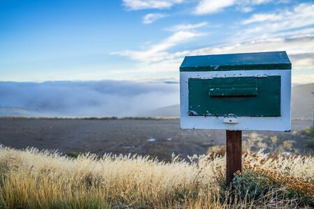 Wooden vintage mailbox in beautiful nature landscape, golden dried grass with small flower and sea of fog and blue sky in the background in cold weather morning.