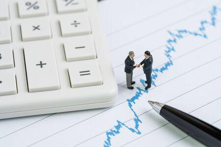 Hombre de negocios de personas en miniatura con apretón de manos de traje en la tabla de precios de acciones con calculadora y bolígrafo usando como negociación de guerra comercial, hablar y cumplir con el precio de mercado de valores de ese efecto. Foto de archivo