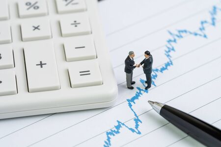 Miniature people businessman with suit handshaking on stock price chart with calculator and pen using as trade war negotiation, talk and meeting that effect stock market price.