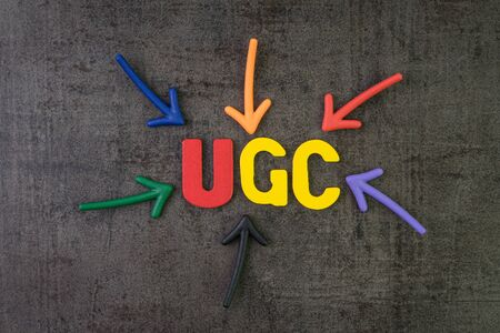 UGC, benutzergenerierte Inhalte mit Online-Werbekonzept für die Markenkommunikation, mehrfarbige Pfeile, die auf das Wort UGC in der Mitte der schwarzen Zementtafelwand zeigen.
