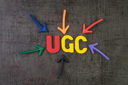 UGC, contenido generado por el usuario utilizando el concepto de publicidad en línea de comunicación de marca, flechas multicolores que apuntan a la palabra UGC en el centro de la pared de pizarra de cemento negro.