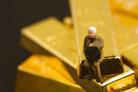 Gold, bullion or ingot in wealth management or investment asset allocation concept, miniature people manager businessman with suitcase sitting on stack of gold bar in dark security room.
