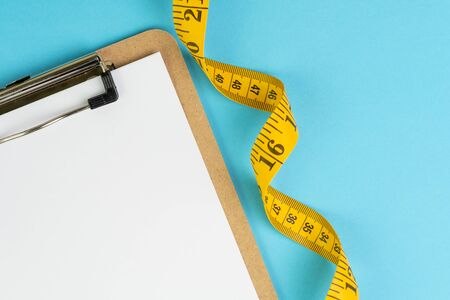 Healthy eating plan, diet or fitness planning, blank white paper on clipboard with measuring tape on solid blue background, writing message to set target or goal, menu or message.
