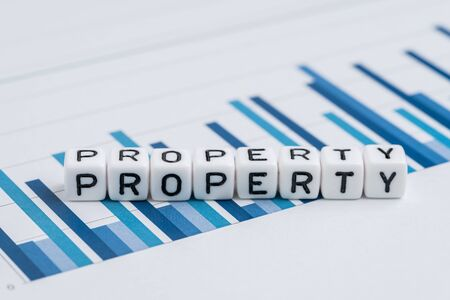 Property, real estate or Reits price analysis concept, small cube block with alphabets building the word Property on yearly chart and graph reports.