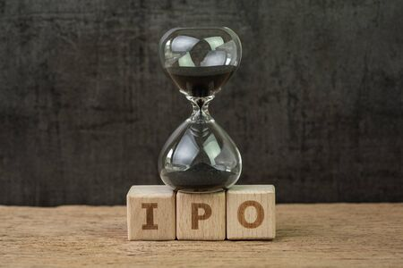 IPO, Initial Public Offering for company to buy and sell in stock market, sandglass or hourglass on wooden cube block with alphabet building the word IPO on wood table, dark black background.