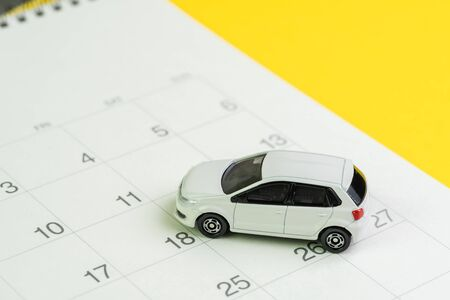 Car loan payment, buying new car or yearly maintenance schedule concept, miniature white car on clean calendar with date on yellow background.