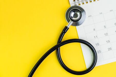 Medical and health care calendar, reminder, schedule or appointment concept, doctors stethoscope on white clean calendar with date on solid yellow background with copy space.