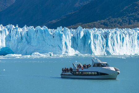 Ferry boat in front of Perito Moreno glacier, blue ice burg glacier from peak of the mountain through the blue lake in Los Glaciares National Park, Santa Cruz, Argentina, southern Patagonia ice field. Stock fotó