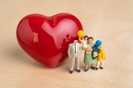 Happy family, perfect parental love with bright future, miniature people happy family dad, mom with children holding balloons with red heart shape on wooden table.