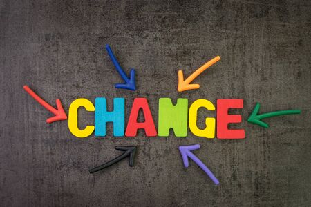 Change management, business transformation or move before disruption concept, multi color magnet arrows pointing to the word CHANGE at the center of dark black cement chalkboard wall background.