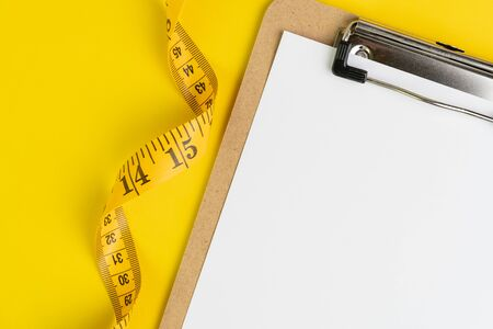 Healthy eating plan, diet or fitness planning, blank white paper on clipboard with measuring tape on solid yellow background, writing message to set target or goal, menu or message. Stock fotó