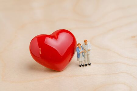 Senior elderly health care, caregiver or happy retirement concept, miniature people happy couple man and lady senior citizen holding each other standing with red heart on wooden table.