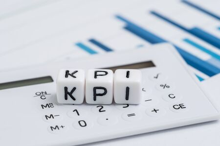 Key Performance Indicator, KPI measurement to evaluate business success, white cube block with alphabets building the word KPI on calculator over bar graph reports.