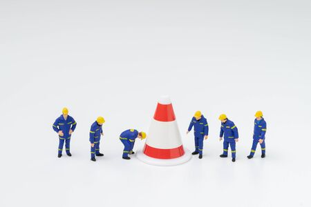 Miniature people figure workers with uniform working with big pylon on white background using as under construction, being fixed or repair or start building something with safety.