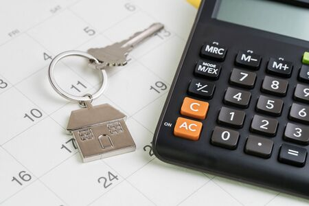 New house purchase, mortgage schedule reminder or real estate payment day, silver house keyring with calculator on white clean calendar. Stock fotó