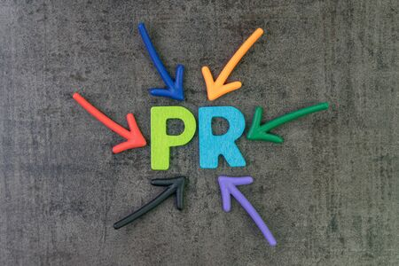 PR, Public Relation concept, multi color arrows pointing to the abbreviation PR at the center of black cement chalkboard wall, the activity to promote company.