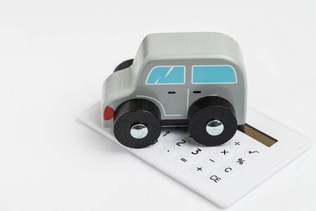 Car leasing, insurance or purchase calculation, maintenance cost concept, miniature toy wooden car on small calculator on white background. Stock fotó