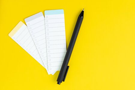 Business idea check list, planning for shopping reminder or project priority task list, black pen on small notepad with checkbox on solid yellow background with copy space.