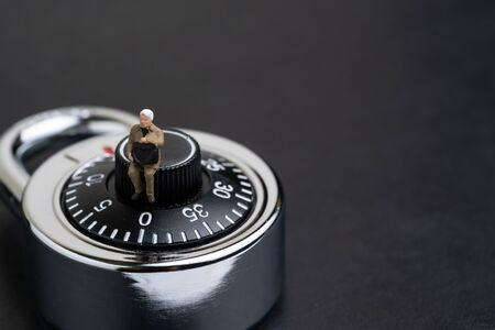 Security, information safety or user privacy concept, miniature people businessman in suit holding secret briefcase sitting on combination lock pad number passcode on black background with copy space.