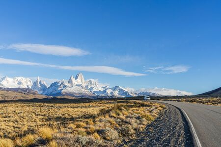 Beautiful asphalt road Route 40 with background of Fitz Roy and Cerro Torre peak snow mountain in the morning blue sky with golden yellow grass in autumn, El Chalten, south Patagonia, Argentina.