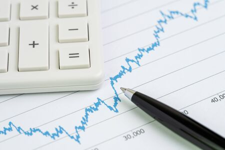 Stock price growth chart with calculator and pen using as financial analysis, stock market report or information for investment.