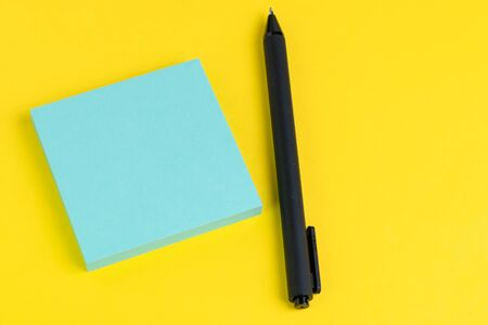 Pen with tack of sticky notes on solid yellow background with pink, yellow and blue on top with copy space for writing message using as memo, reminder or record idea.