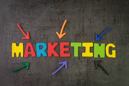 Marketing, commercial strategy for company to promote to sell product and services concept, multi color arrows pointing to the word Marketing at the center of black cement chalkboard wall. Stock fotó